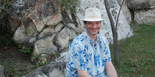 A man wearing a white hat sits on a rock with a rocky nature scene behind him