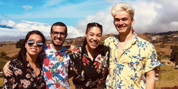 Four people in flower shirts with their arms around each other smiling with blue sky